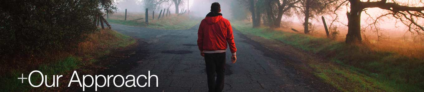 A man walking toward a fork in the road. Austin+Koffron's approach is to help you determine your path to your future.